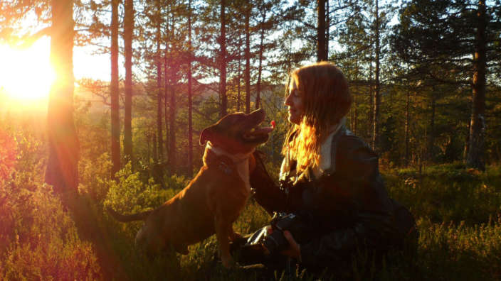 Woman-and-dog-in-forest-at-sunset
