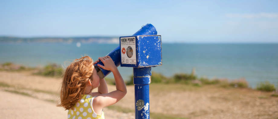 Girl Looking Through Viewfinder At Milford On Sea Beach Clifftop
