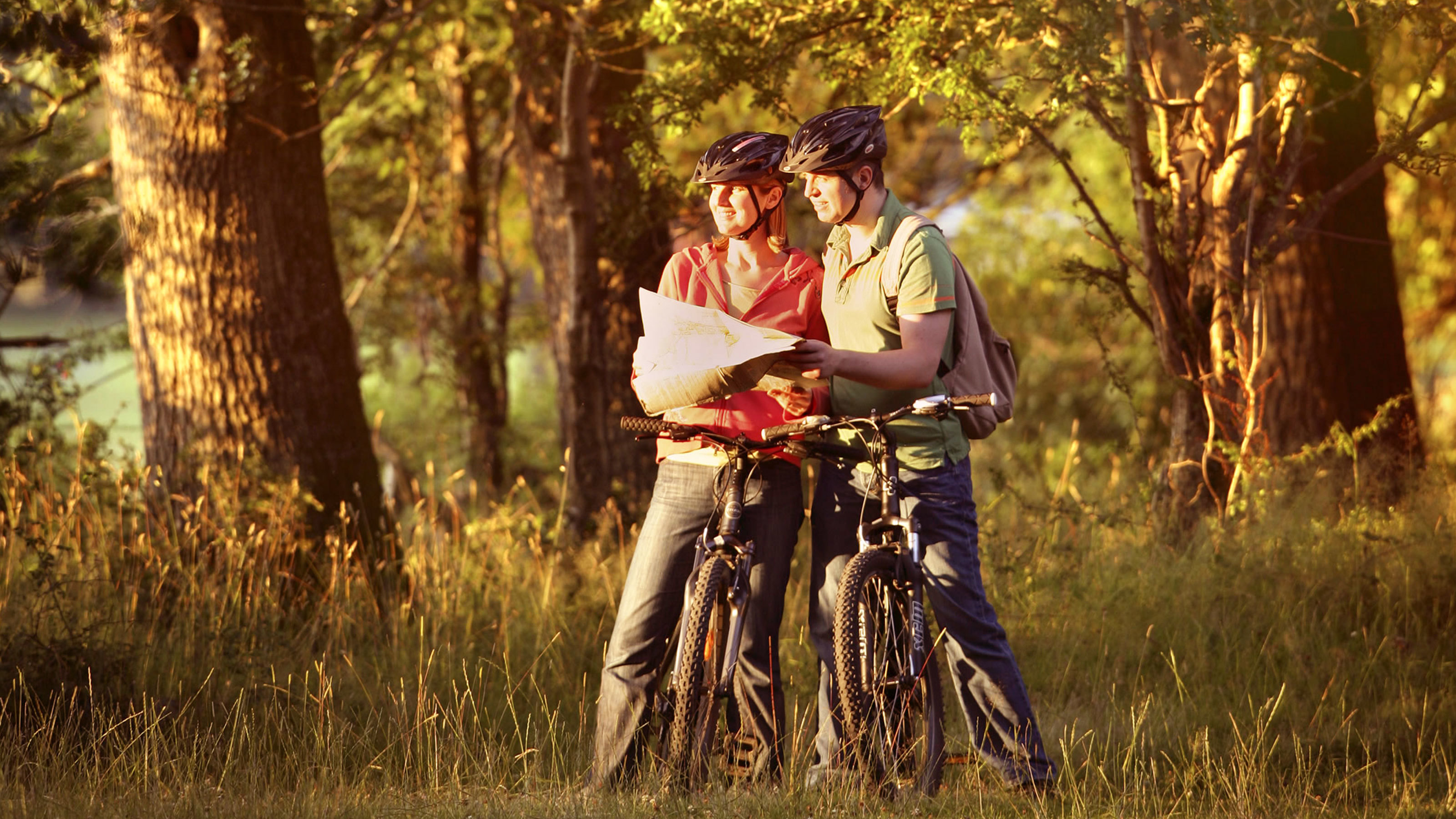 Couple reading map whilst cycling