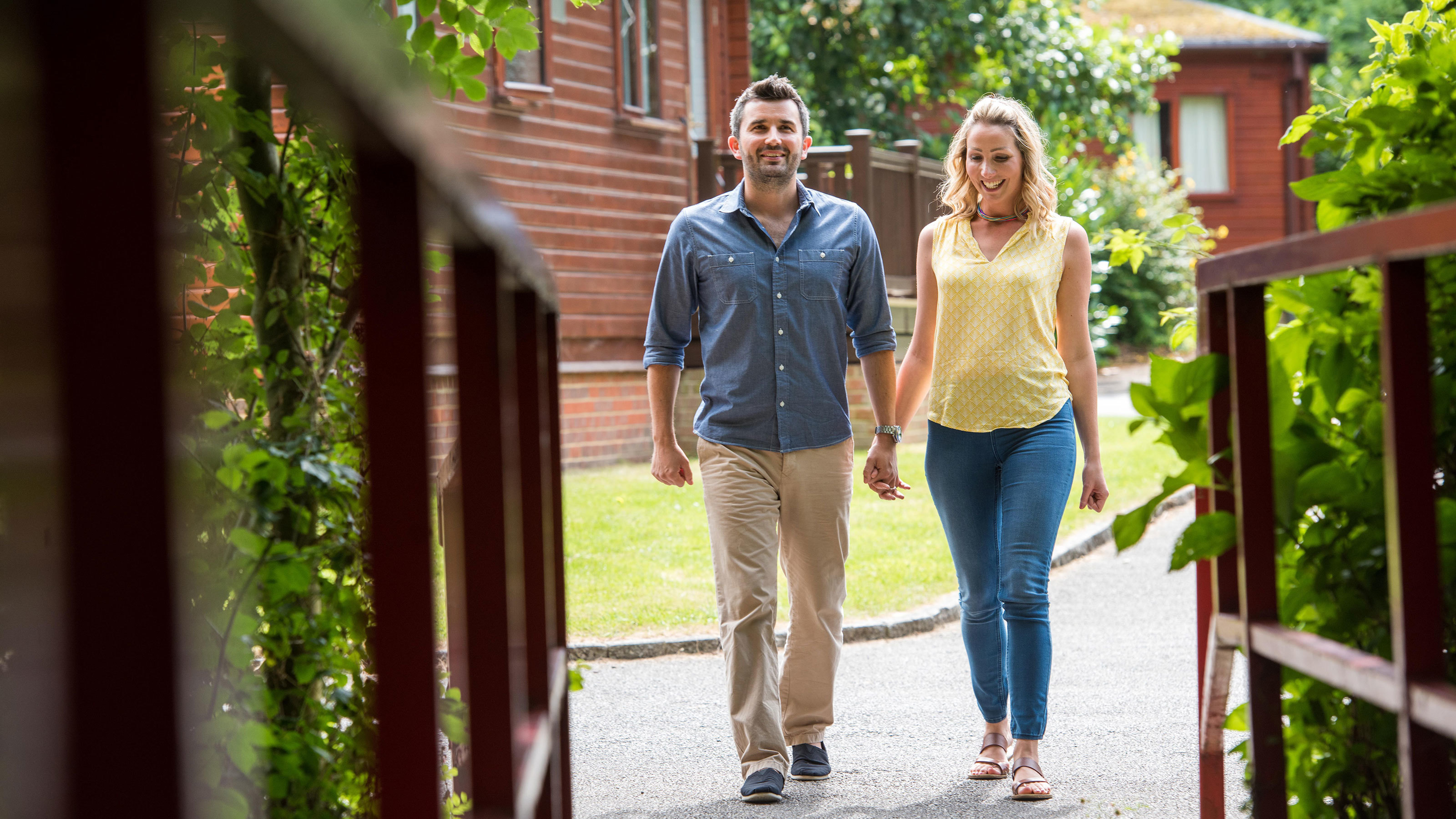 Couple walking through woodland and lodges in summer at Shorefield Country Park