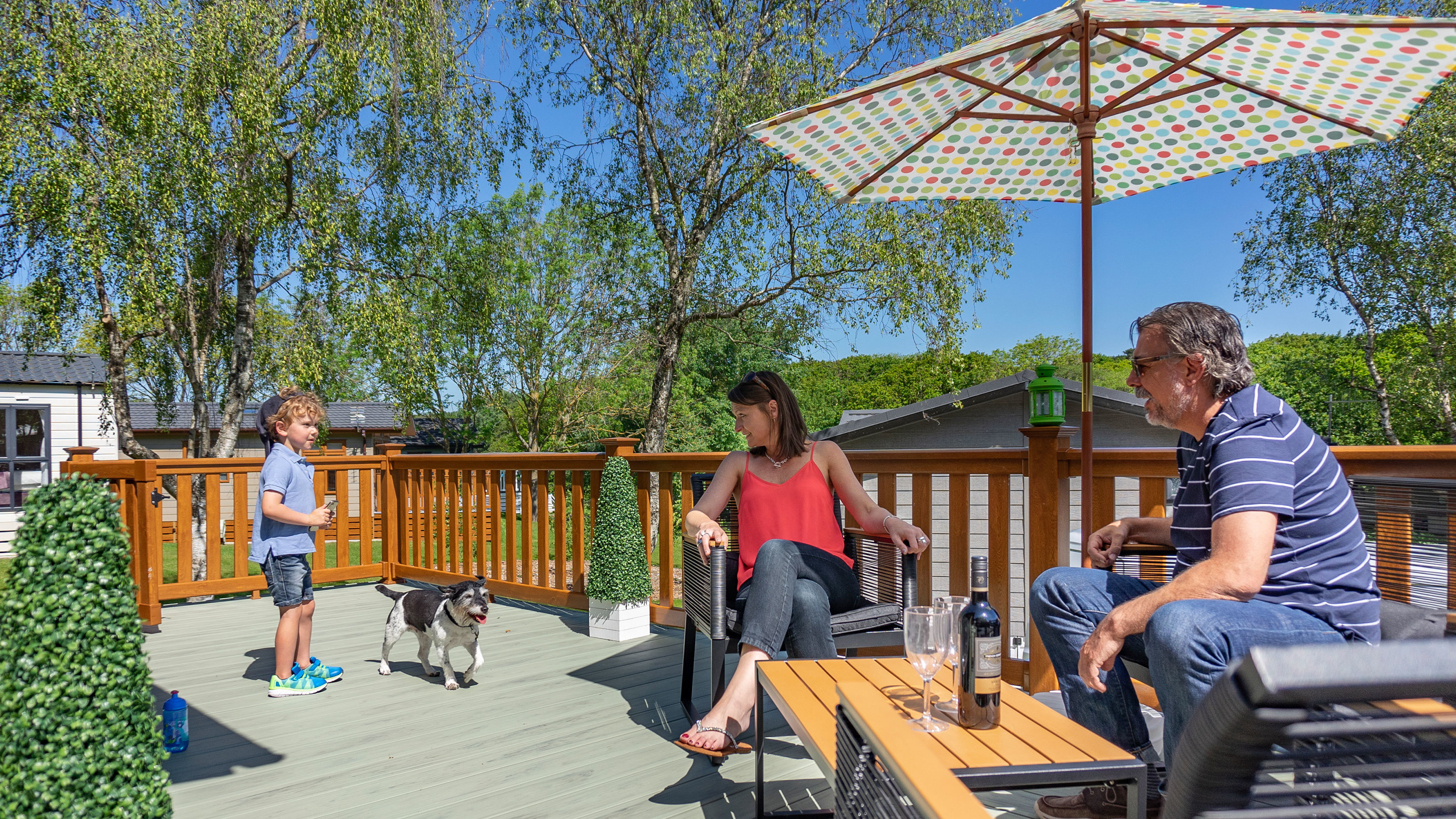 Family-enjoying-th-sunshine-on-the-decking-of-their-holiday-home