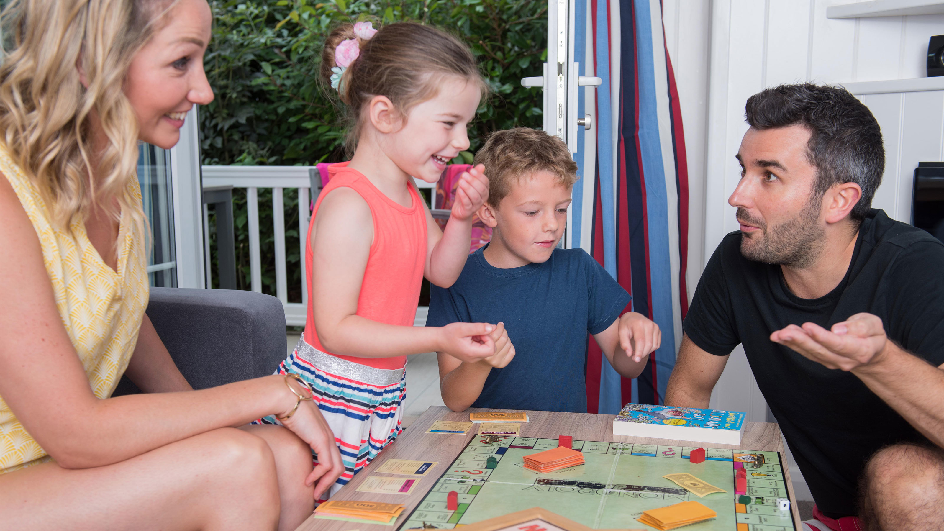 Family-playing-monopoly-board-game-in-accommodation