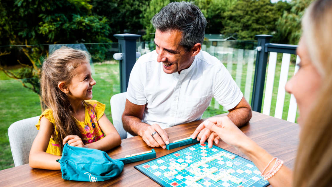 Family-playing-scrabble-on-decking-of-holiday-home