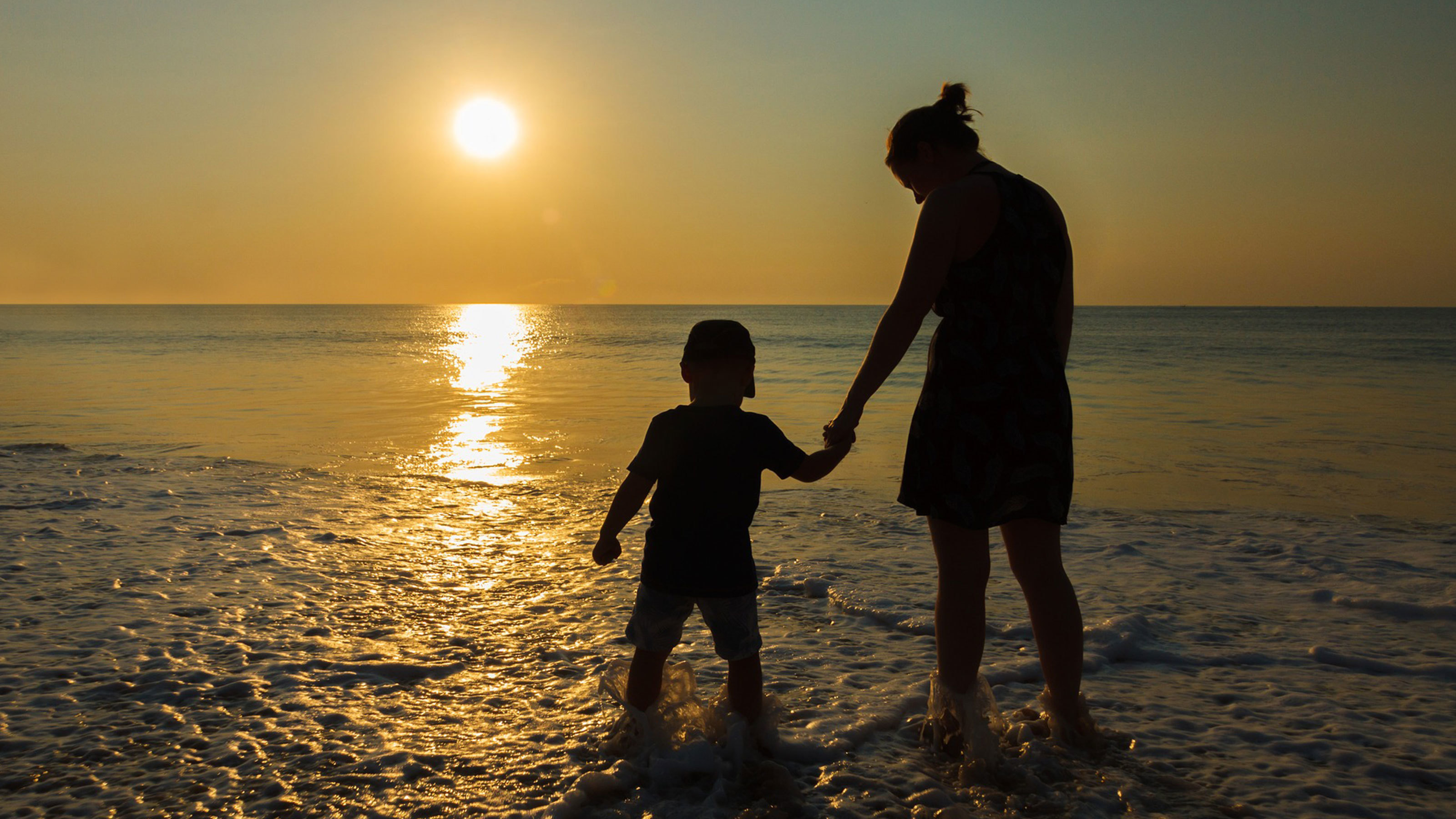 Mother-and-child-paddling-in-sea-at-sunset