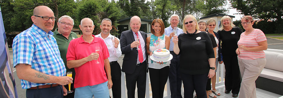 Staff celebrate with champagne and a cake