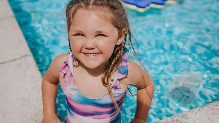 Girl swimming in outdoor pool at a Shorefield Holidays park