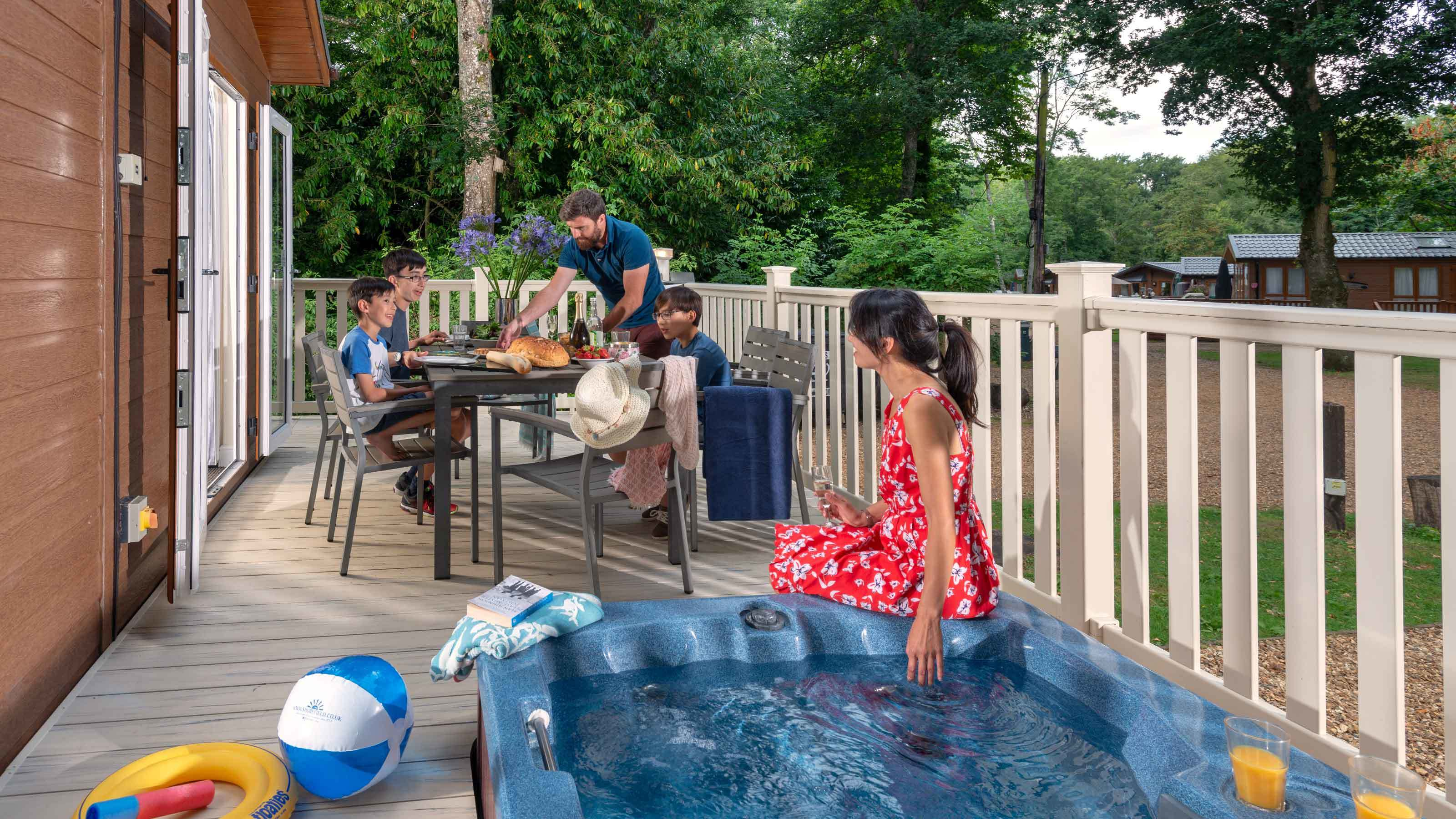 Family enjoying meal on decking of hot tub lodge