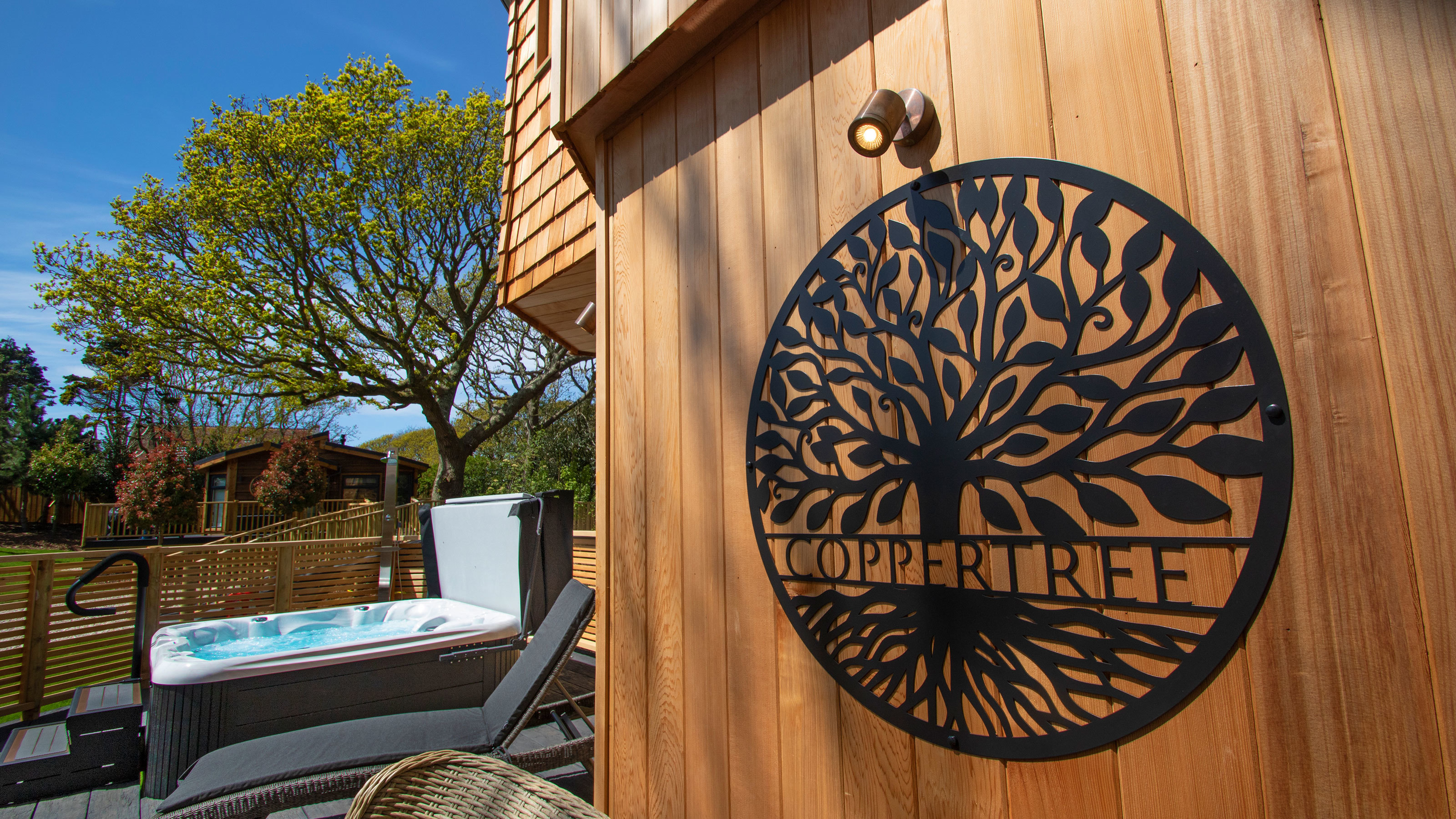 Coppertree sign on treehouse exterior with hot tub