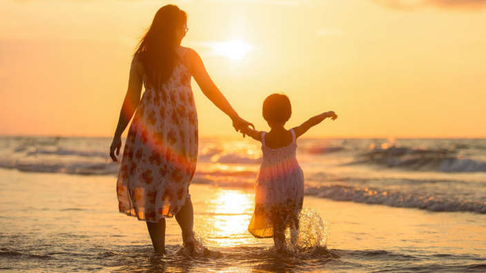 Mother and child on beach at sunset