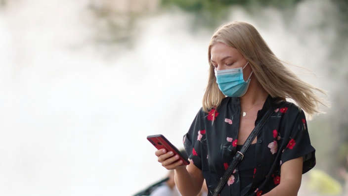 Woman wearing a face mask whilst looking at phone