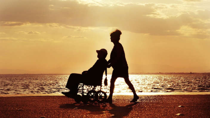 Couple on beach with wheelchair at sunset