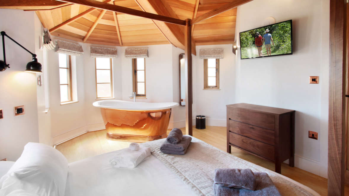 Master bedroom with freestanding copper bath treehouse accommodation with Shorefield Holidays