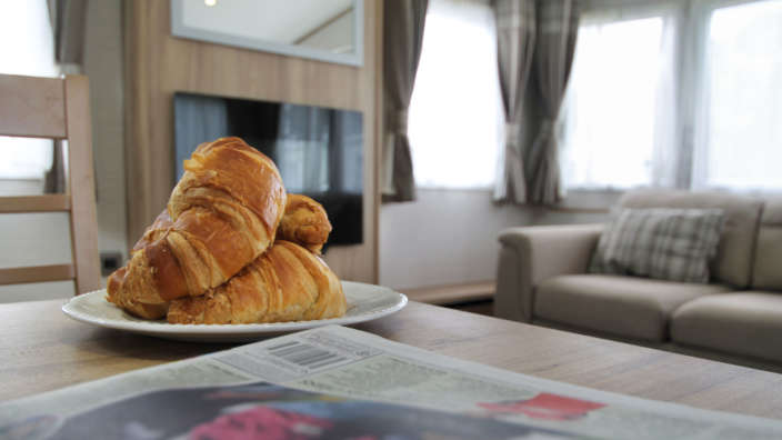 4 Croissants And Newspaper On Caravan Table