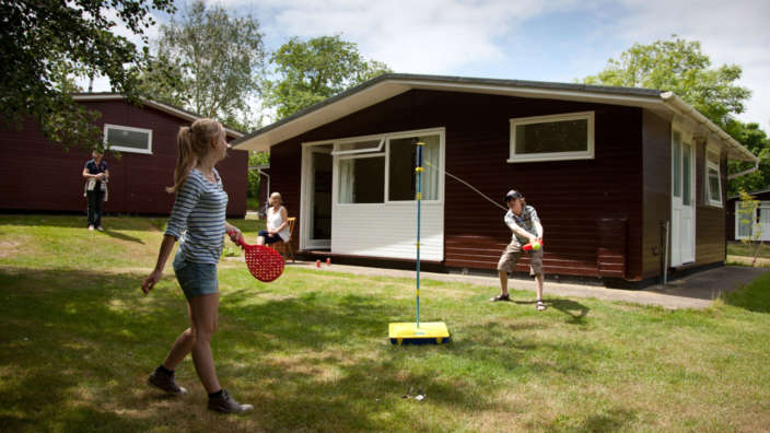 Family Playing Swingball Outside Chalet