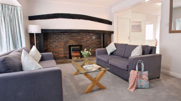 The Burrow lounge with cosy traditional fireplace