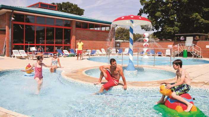 Family Making A Splash In The Outdoor Pool At Oakdene Forest Park