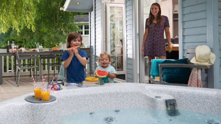 Two-children-eating-watermelon-with-mum-on-decking-of-a-hot-tub-lodge-special-offers
