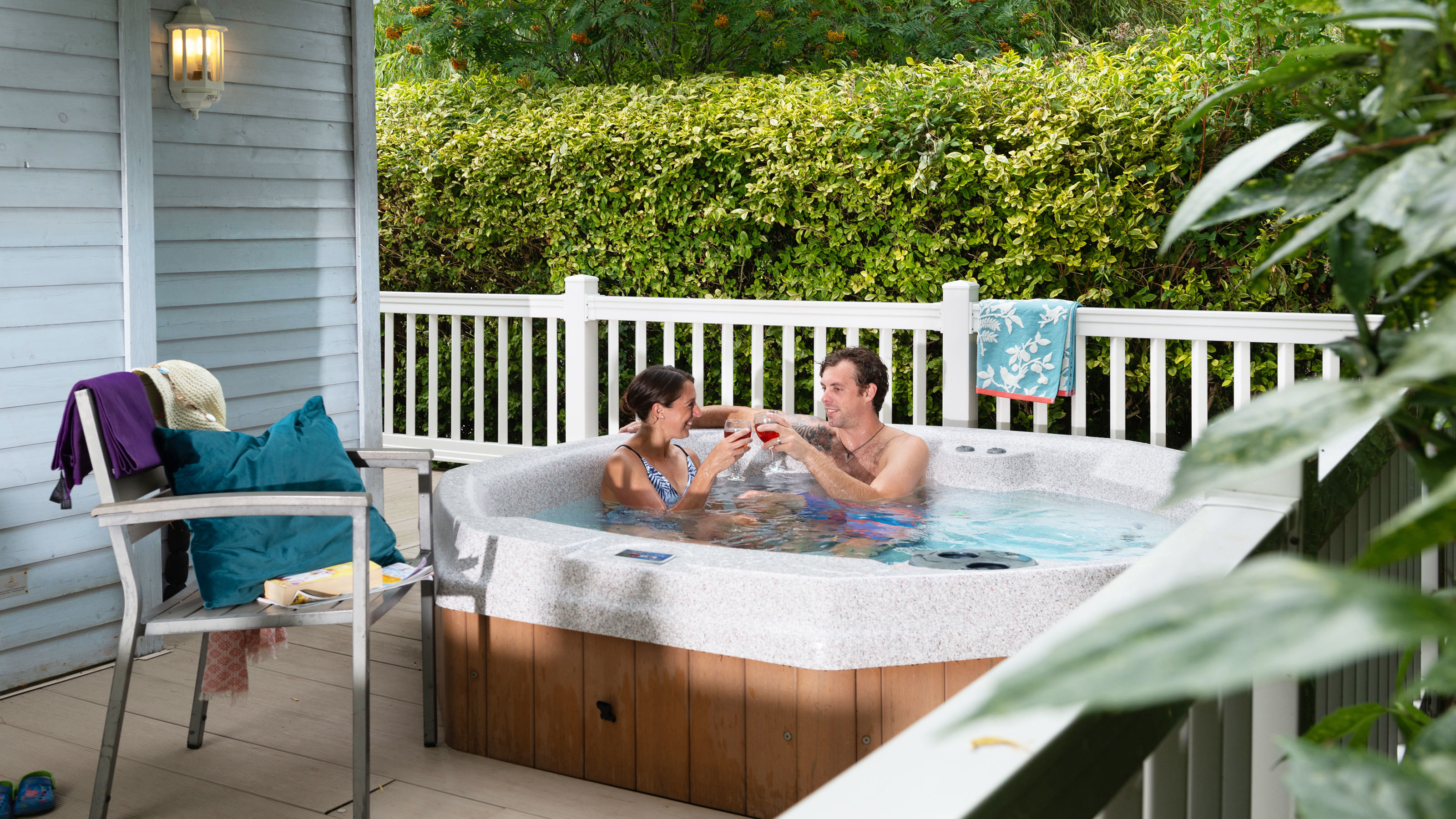 Couple-relaxing-with-a-glass-of-wine-in-hot-tub