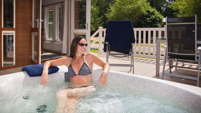 Woman Enjoying Hot Tub Holiday Woodland Lodge