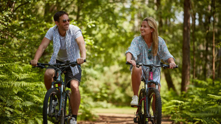 Couple Cycle Through A Leafy Forest Canopyt