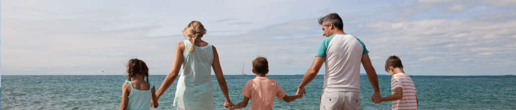 Family Paddling In Sea In Summer