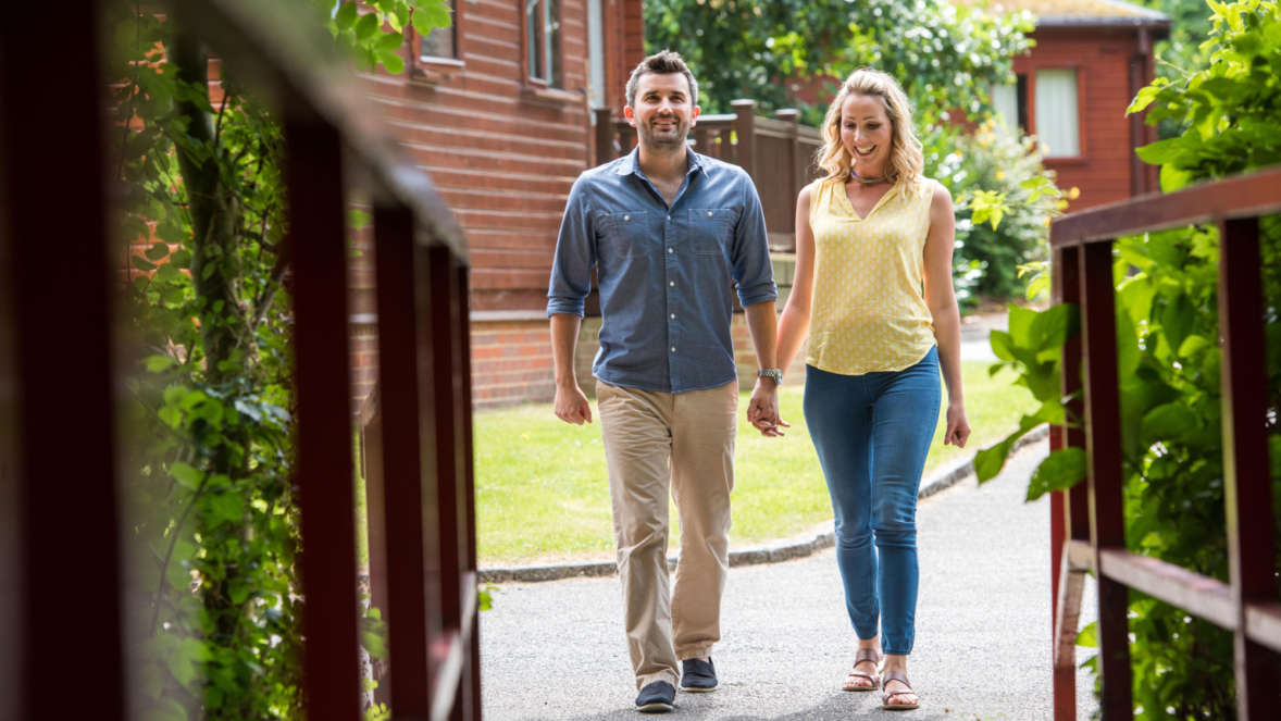 Couple Walking Through Lodges At Shorefield Country Park In Spring