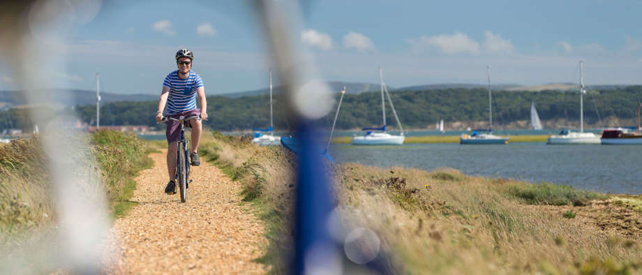 Man Cycles Along Hurst Spit At Milford On Sea