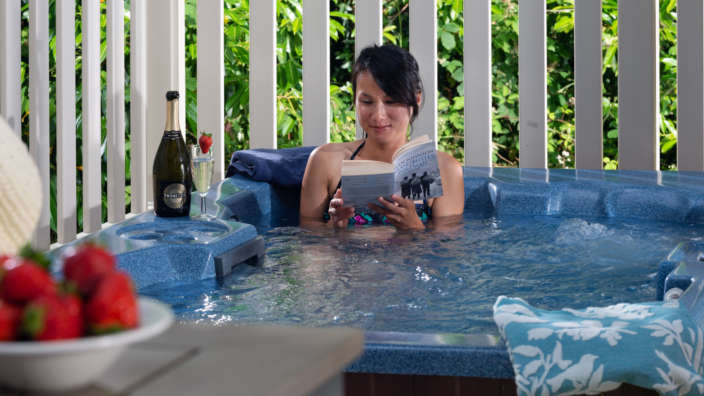 Woman-relaxing-in-hot-tub-reading-book