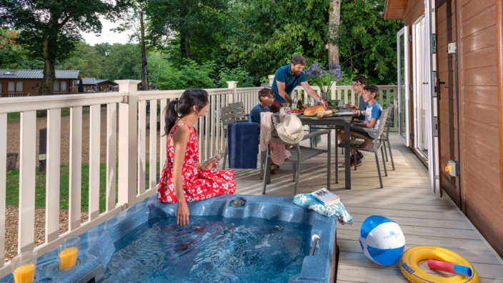 A-family-on-decking-of-signature-hot-tub-lodge