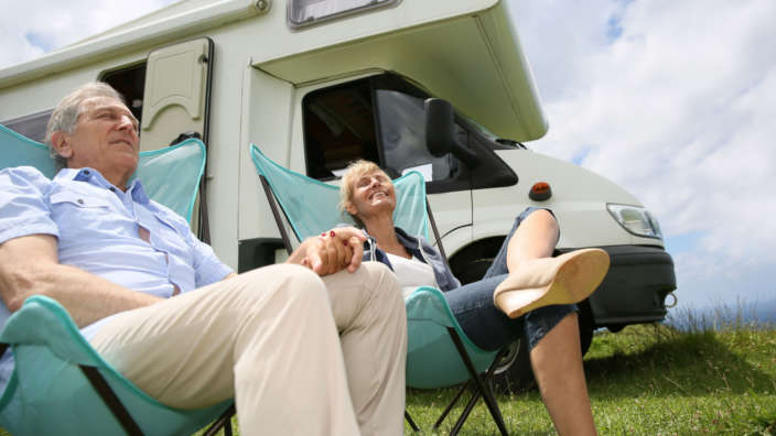 Couple relaxing next to their motorhome