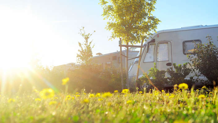 Touring caravan in field with sunshine and lens flare