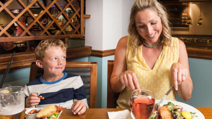 Woman And Child Eating Dinner In Tides Bar Discount Benefits