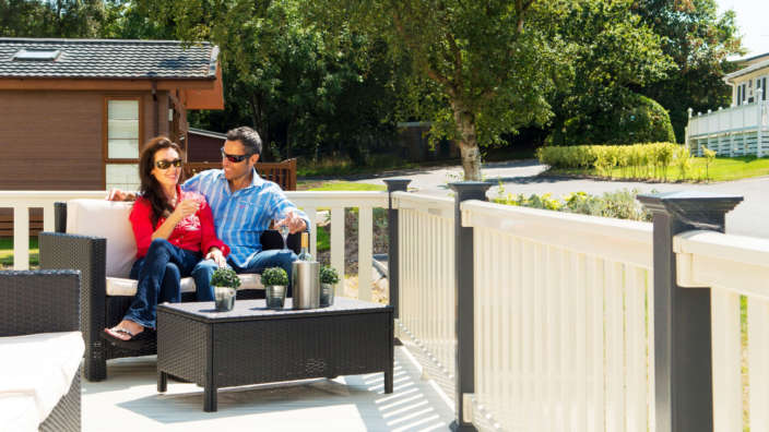 Couple Relaxing On Private Veranda Of Holiday Home