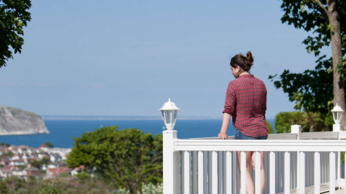 Woman On Holiday Home Decking Overlooking Swanage Bay