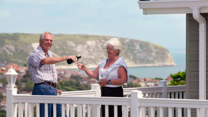 Couple Enjoying A Glass Of Wine On Veranda Of Holiday Home Swanage View