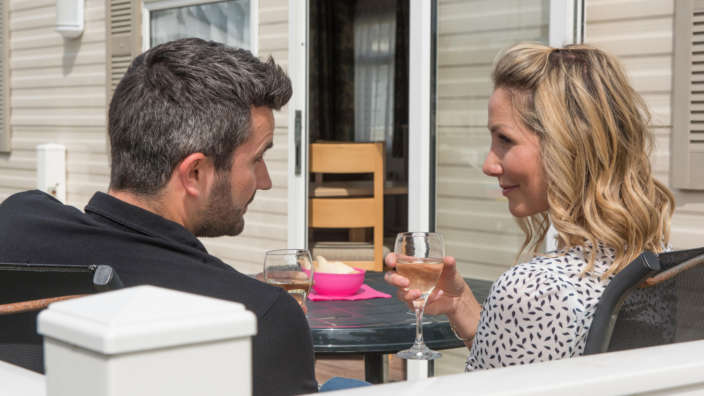 Young couple on decking of their holiday home drinking a glass of wine
