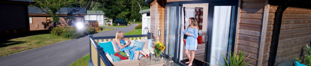 Family on decking of their new forest holiday home header