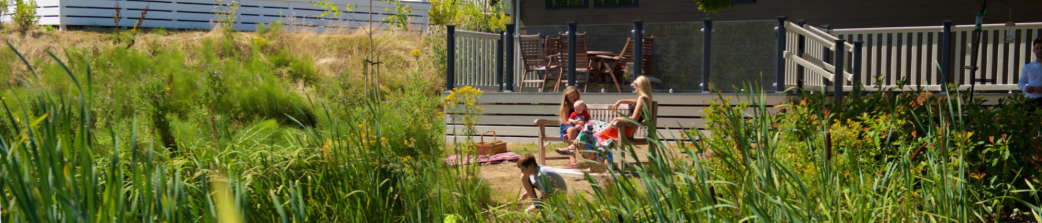 Family-relaxing-by-lodge-in-summer