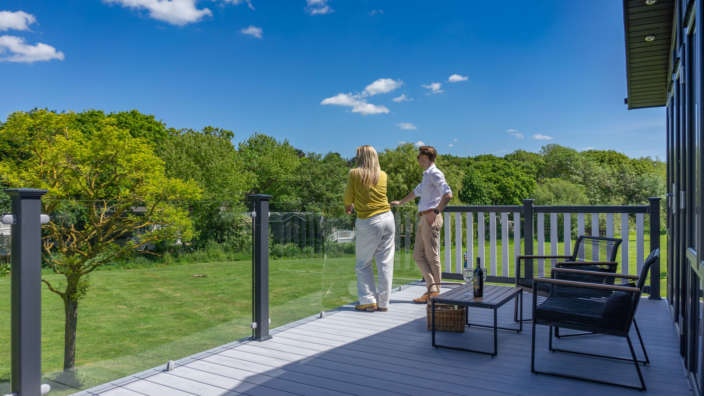 Couple on decking of Hampshire holiday home overlooking parkland