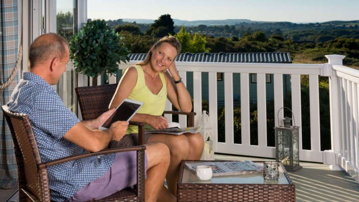 Couple Using Wifi On Decking With Views Over Countryside