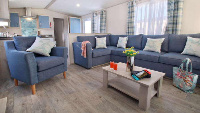 Spacious lounge with L shaped sofa in seaside caravan accommodation