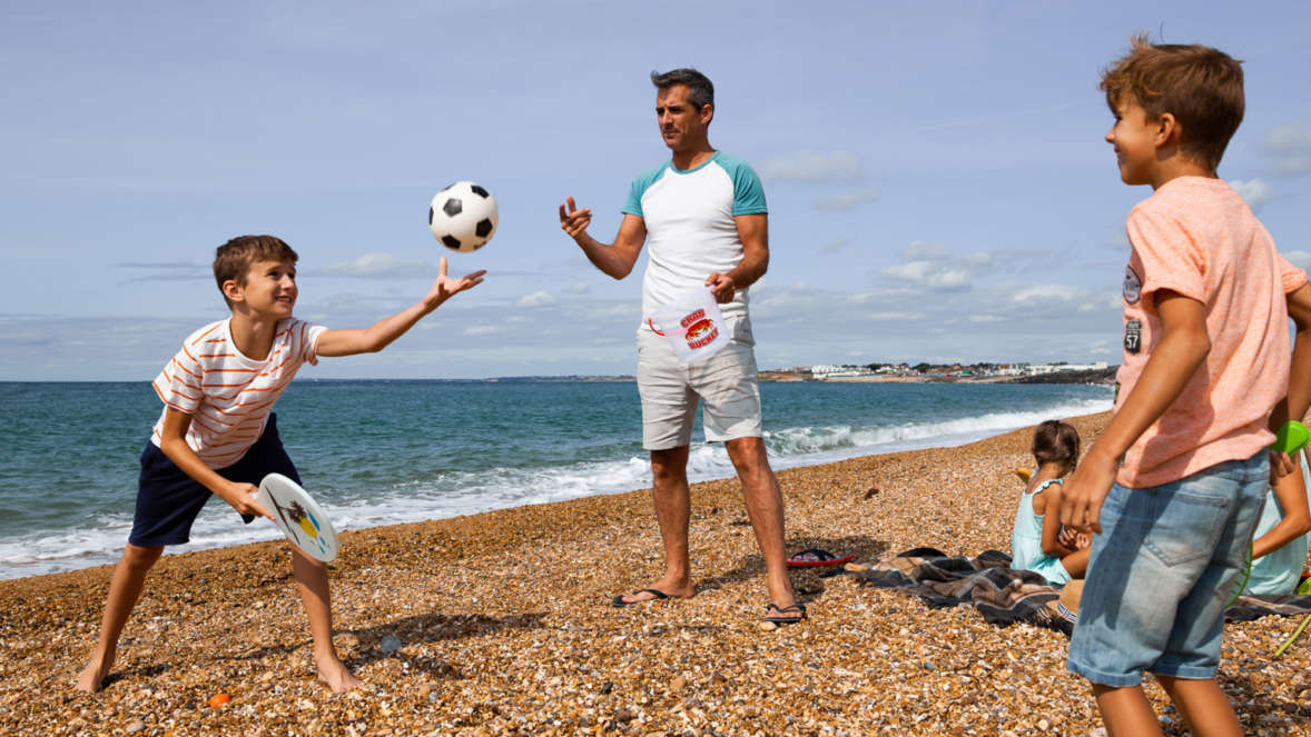 Family-playing-football-on-milford-on-sea-beach-in-the-new-forest