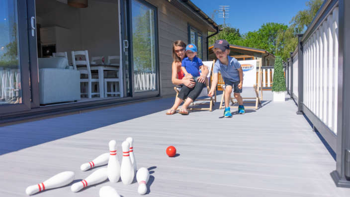Young boy playing skittles on decking of holiday home